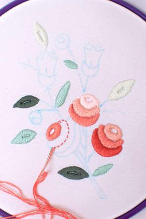 punto de cruz: Bordado con motivo floral enmarcado en aro. Trabajo en proceso. Cierre, foco selectivo suave.