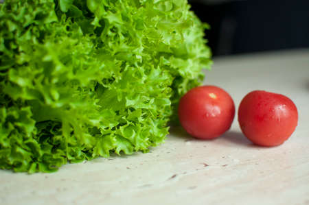 Bunch of raw organic green frisee salad and two tomatoes on wooden table. Selective focus. Stock Photo