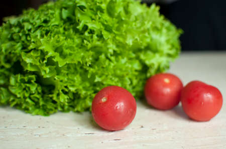 Bunch of raw organic green frisee salad and three tomatoes on wooden table. Selective focus. Stock Photo