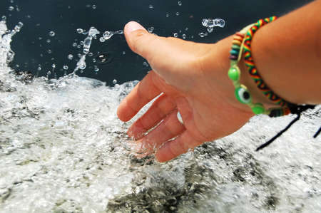 foaming: Female hand touching splashes of foaming water while floating on engine boat. Close-up picture. Stock Photo
