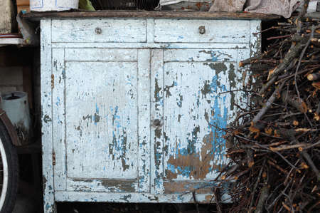 Close-up of ancient light blue vintage rustic commode bureau with paint peeled off. Rural yard.