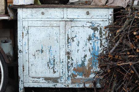 Close-up van oude lichtblauwe uitstekende rustieke ladenkastdienst met weg gepelde verf. Landelijke tuin.