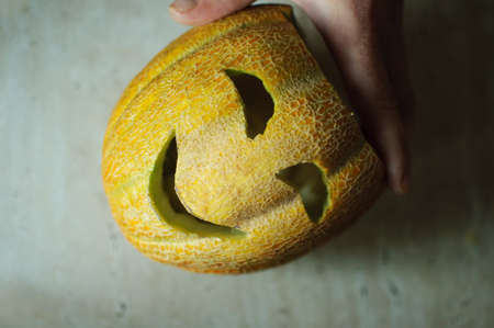 tradition: Unusual Halloween melon, cutting process, knife and male hands. Selective focus and bokeh.