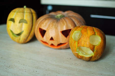 Three jack-o-lanterns from pumpkin and melons on kitchen table. Concept Halloween background Stock Photo