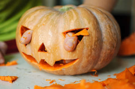 Process of making Jack-o-lantern. Funny picture of Halloween pumpkin monster face with male fingers. Selective focus and bokeh. Stock Photo