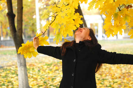 A funny young attractive girl has fun and fooling around in an autumn park. Cheerful emotions, autumn mood.