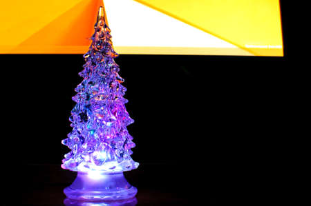 A small lighting Christmas tree on the contrast dark and orange geometric background. Selective focus, reflections, geometric lines. Abstract colorful Christmas background.