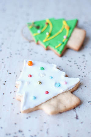 Two gingerbread cookies in the shape of the green and white Christmas tree on the background of a wooden table and scattered chia seeds. Top view, selective focus, bokeh. Stock Photo