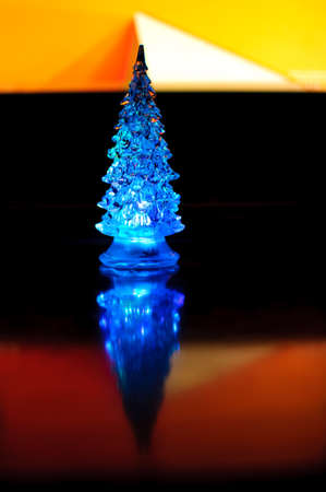 A small blue lighting Christmas tree on the contrast dark and orange geometric background. Selective focus, reflections, geometric lines. Abstract colorful Christmas background. Stock Photo