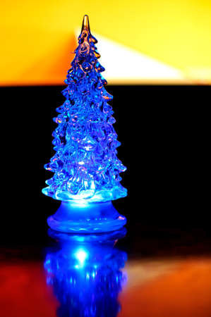 A small lighting Christmas tree on the contrast dark and orange geometric background. Selective focus, reflections, geometric lines.