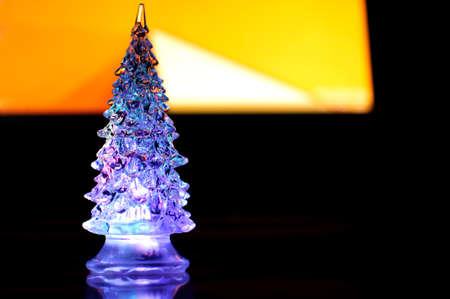 a small lighting christmas tree on the contrast dark and orange geometric background selective focus - Small Purple Christmas Tree