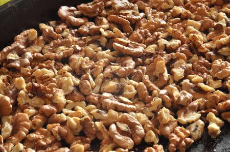 Baked walnut kernels on a black backing tray close-up. Walnut background