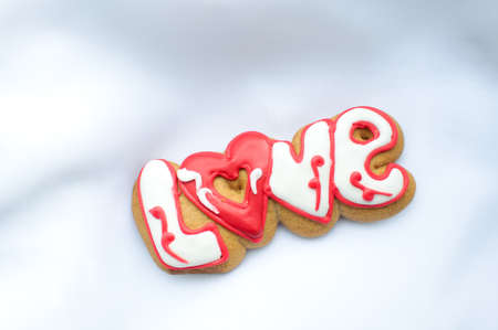 Letter cookies for Valentines day or for a wedding day on the background of white lightweight fabric.