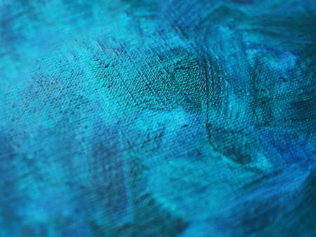Texture of a canvas with large brushstokes of blue oil paint. Close-up, selective focus.