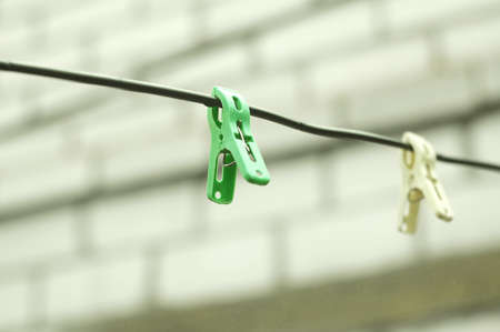 Two clothespins on a rope on the background of a brick wall of house. Selective focus