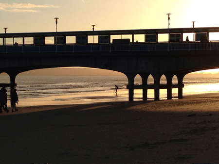 bournemouth: A guy surfing as the sun sets on Bournemouth beach