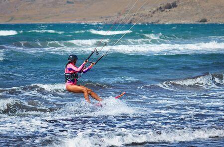 man kiteboarder kitesurfing unhooked at sunset and jumping rotations  athlete jump boy