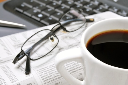 Coffee cup, glasses, financial newspaper, pen, and computer keyboard, in the office.
