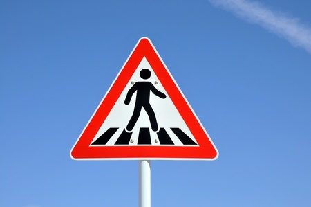 Pedestrian crossing sign on blue sky background photo