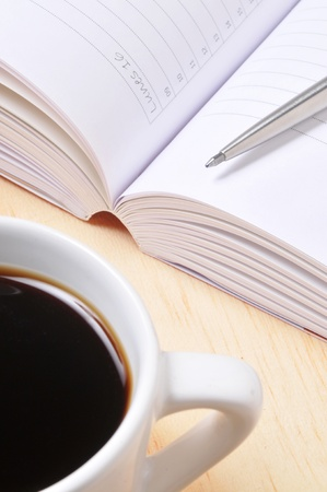 Workplace: open note book with pen, and coffee cup. Stock Photo