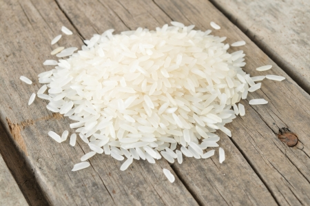 Raw rice on wooden table  Stock Photo