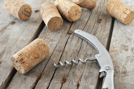 Corkscrew and wine corks on rustic table   Stock Photo