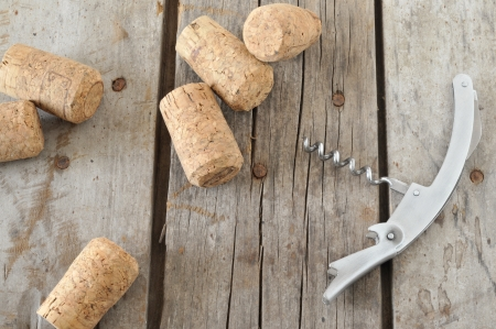 Corkscrew and wine corks on rustic table.