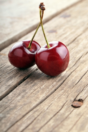 Two cherries on rustic table