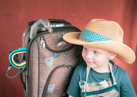 turistic: Child in Hat and Scuba mask near Suitcase looking left Stock Photo