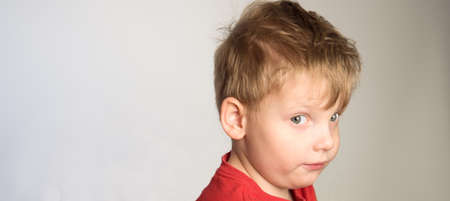 Little boy in red t-shirt is curious about something