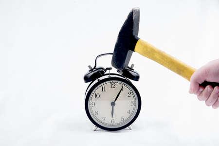 Close up view of hammer is crashing alarm-clock
