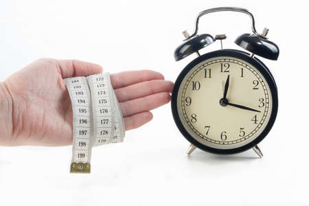 beat the clock: Hand with measuring tape and alarm clock on white background Stock Photo