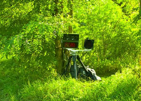 Radarkontrolle  Mobile speed camera camouflaged in the forest against exceeding the speed limit Foto de archivo