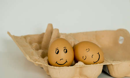 making a face: Close-up of loving relation represented by two eggs in a cartoon box