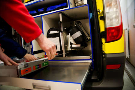 emergency vehicle: Paramedic gets his Expired Air Resuscitation from the back of emergency vehicle with open door and equipment inside. EMS  Stock Photo