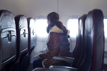 Young woman is on passenger seat at airplane, looking outside