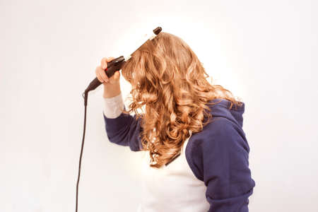Young beautiful woman using modern hair curling  iron to make new stylish hairstyle. Stock Photo