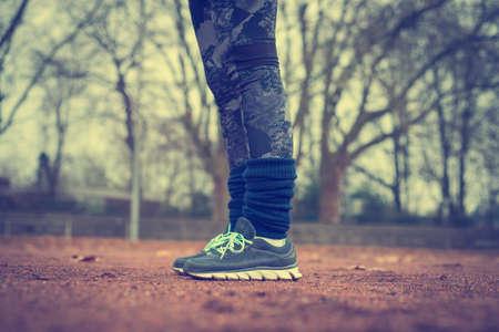 Runner legs on red running track at stadium or sports field.