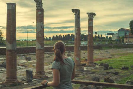 A woman near the great marble column of old building tempel. Tourist at the Museum excavations of the ancient city Foto de archivo