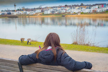 Woman stands on a beanch and looks at beauty of amazing pictorial landscape of European style city with interesting buildings and beautiful lake in which buildings are reflected Foto de archivo