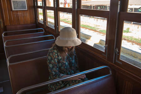 A woman in a vintage dress and hat with the hands on a train background on a sunny day. Portrait of a fashionable woman in retro style. Foto de archivo
