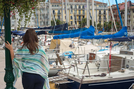 Tourist woman resting in a famous resort destination with yachts in a sea port leaning on street light under nice sommer flower arangement