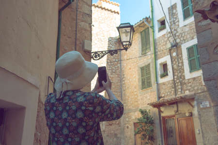 Back view of a young female wanderer out sightseeing in a foreign city during trip overseas, trendy woman traveler with a rucksack on her back walking on unfamiliar street during summer adventure