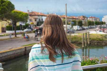 Woman  looking at a new neighborhood of luxurious and exclusivist houses on the lake shore