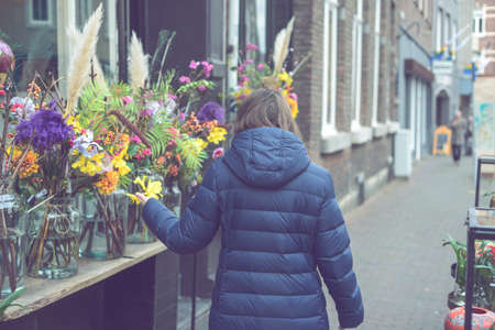 Young smiling woman selecting fresh flowers