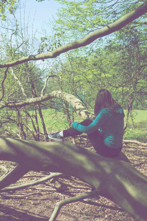 A young woman is sitting on a fallen tree at the end of the forest