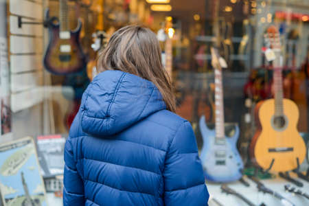 Music selling concept, woman choosing, deciding to buying a new guitar in front of instrument store