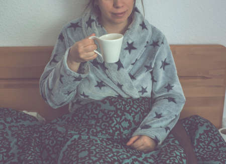 Pretty woman drink coffee from cup with her hand wrapped around a mug of hot coffee enjoying her breakfast in bed