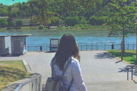 Rear view of woman standing far by railing protection on promenade river, lake