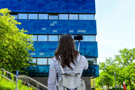 Young woman smiling and taking a selfie with her smartphone in front of a office building Foto de archivo